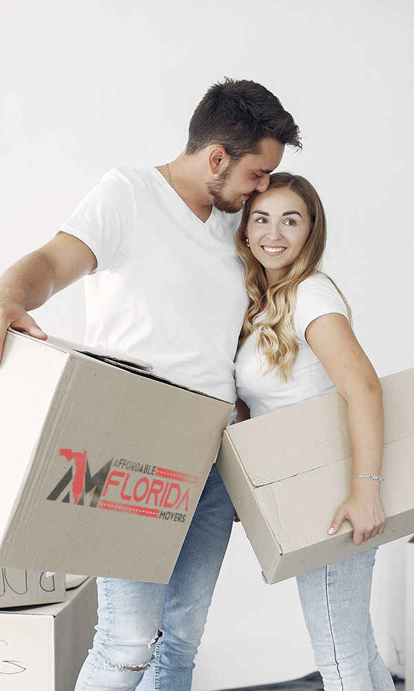 husband and wife holding moving boxes from Affordable Florida Moving
