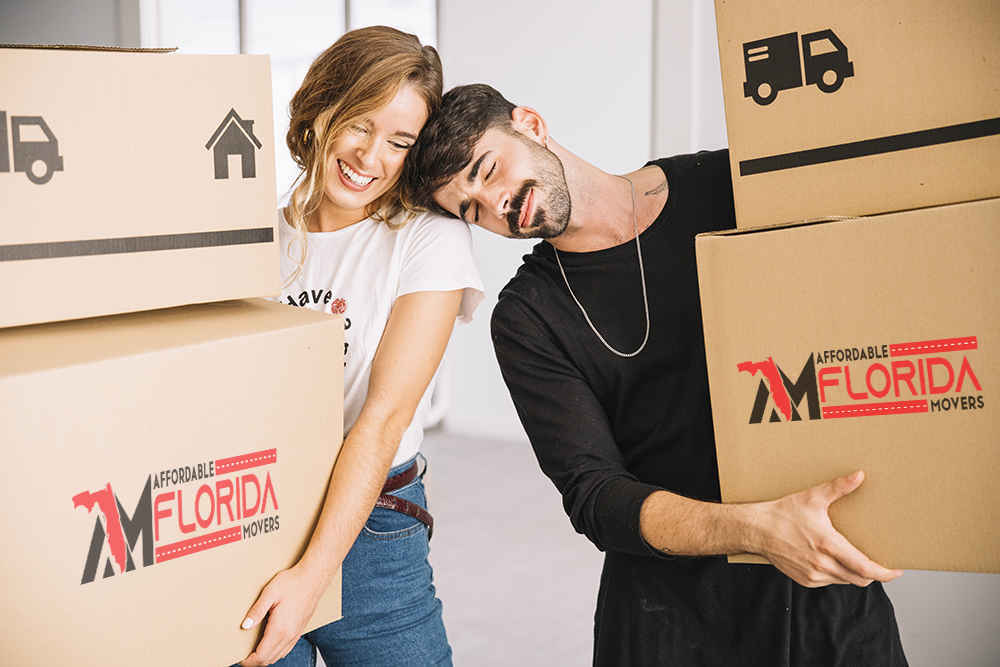 husband and wife walking while carrying moving boxes